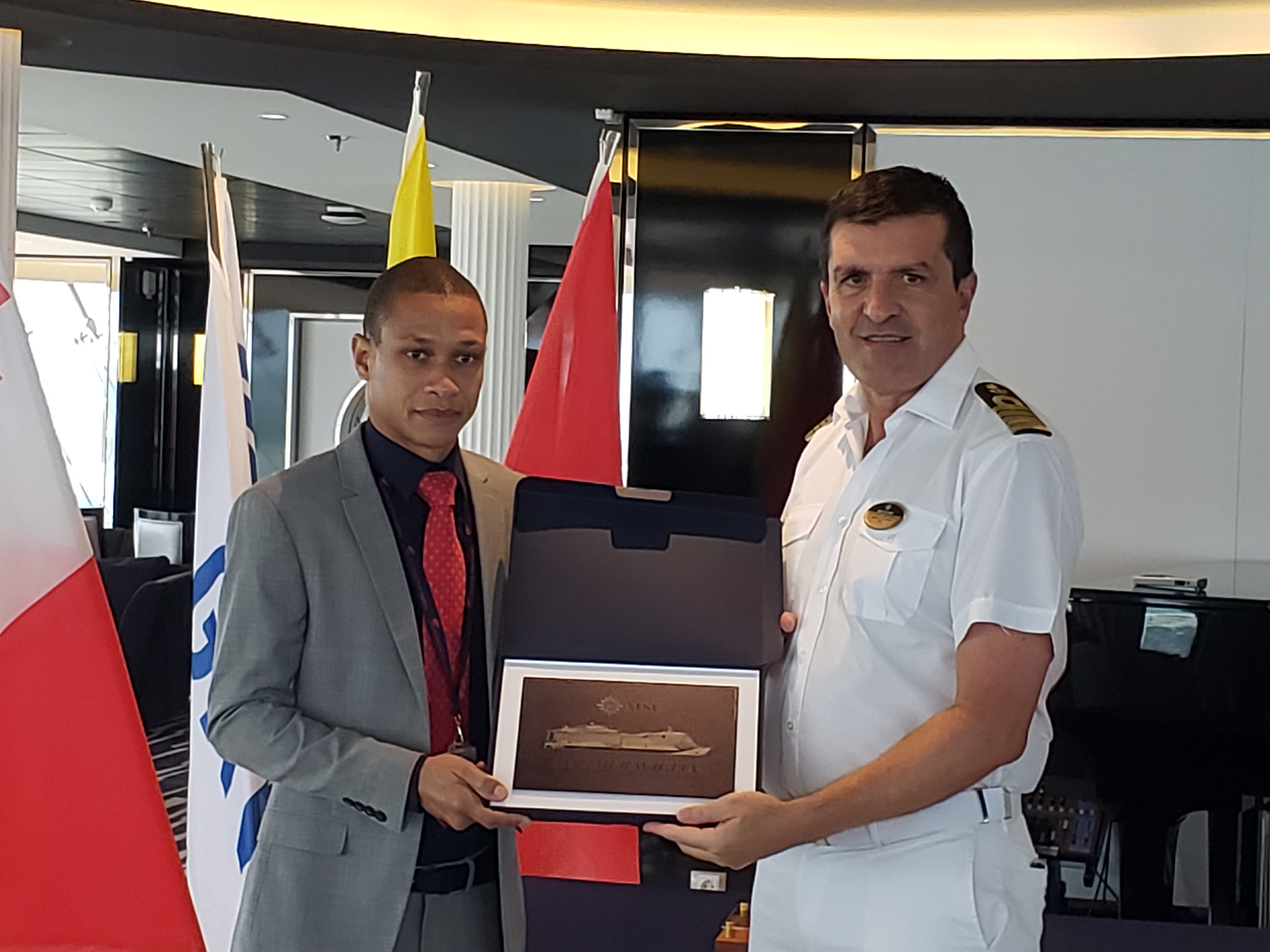 1.	Captain Stefano Battinelli presents a commemorative plaque Platinum Port Agency's Kreigg Yearwood (left).